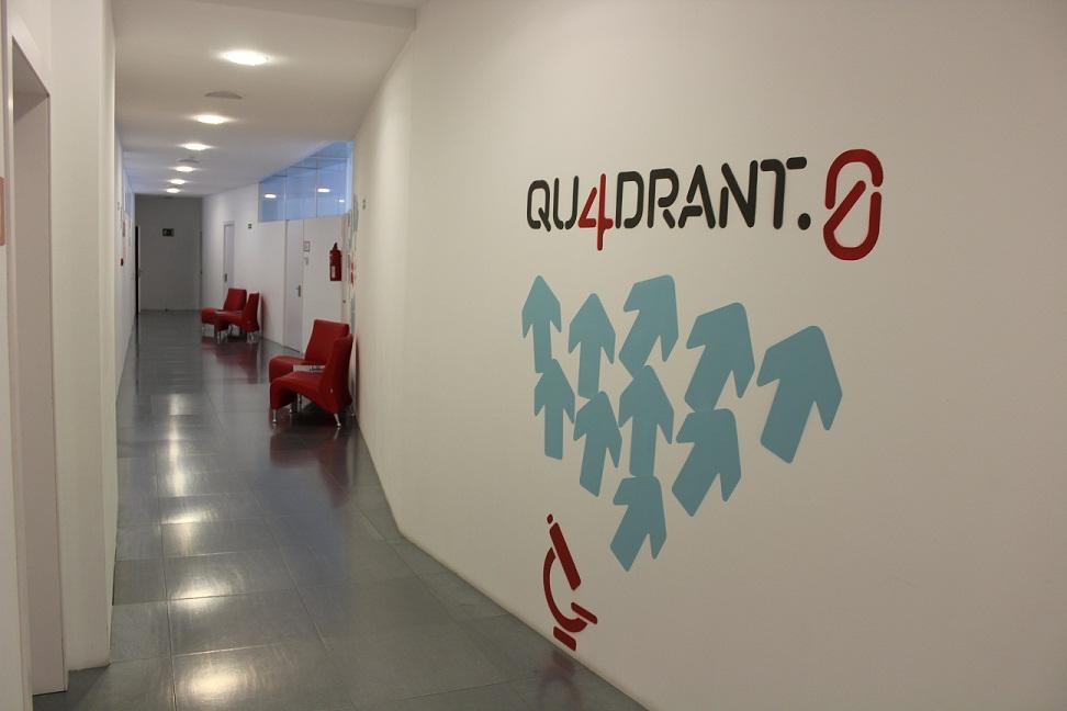 """Imatge passadís Qu4drant.0 on surten cadires, portes de sales i una imatge a la paret blanca amb fletxes blaves i el nom """"Qu4drant.0"""""""
